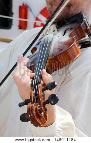 An unidentifiable person plays a violin.