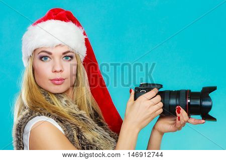 Photographer girl shooting images. Attractive blonde woman wearing santa claus helper hat taking photos with camera. Vivid blue background