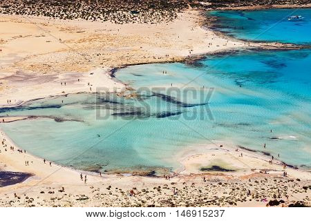 Crete, Greece - 24 May, 2016: Unidentified People Sunbathing And Strolling Along The Beach In Balos