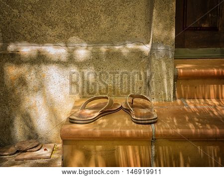 Slippers on the steps of a porch