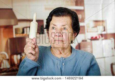 Older cute hispanic woman in blue sweater holding up a rolling pin.