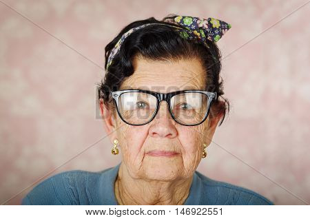 Older hispanic cute woman with flower pattern bow on her head wearing blue sweater and black large framed glasses looking into camera.