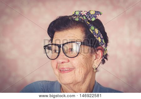 Older hispanic cute woman with flower pattern bow on her head wearing blue sweater and black large framed glasses looking to the side of camera smiling.