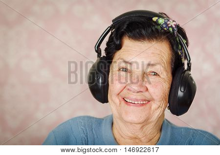 Older adorable hispanic woman wearing blue sweater, flower pattern bow on head in front of pink wallpaper with large black earmuffs smiling to camera.