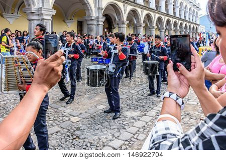 Antigua Guatemala - September 15 2015: Spectators take photos of street parade during Guatemalan Independence Day celebrations outside the Palacio de los Capitanes Generales (Captain General Palace)