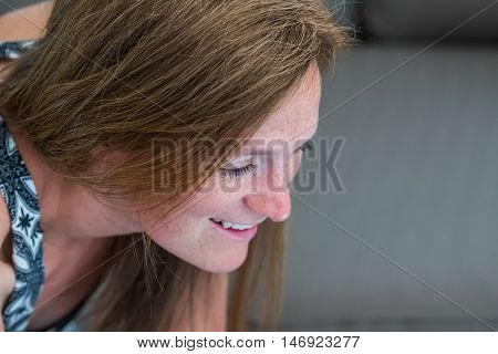 Close Up of Woman Candidly Looking at Something and Smiling with copy space to right