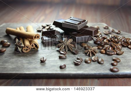 coffee, chocolate, cinnamon and anisetree on a wooden background