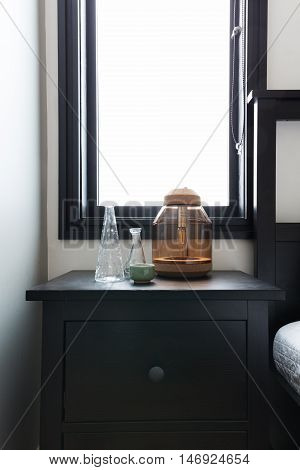 Close up of bedside table with ornaments and bright window behind with space for text