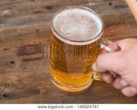 Men's hand holds a mug of light beer on a dark vintage wooden boards.