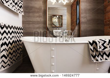 White free standing vintage style bath tub with chevron pattern balck and white towels