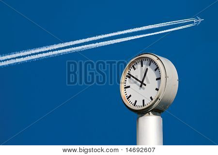 High blue sky and a jet airplane with contrails in the Background. City clock in the Foreground