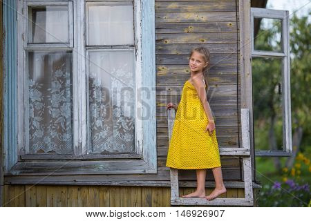 Little girl in a yellow dress standing on a wooden ladder near the farmhouse.