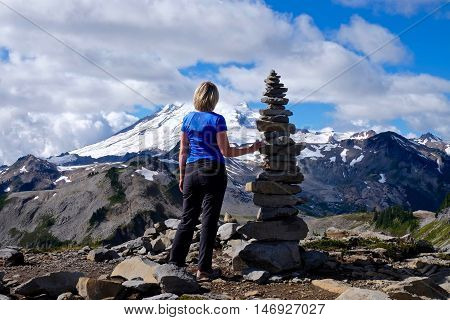 Woaman on mountain top with stone cairn against snow capped Mount Baker. Cascade Mountains. Mount Baker National Forest. WA, USA.