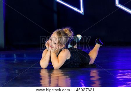 An adorable little tap dancing girl lays on the stage with her chin in her hands and her head tilted to the side kicking her feet. The stage lights give the image a blue tint.