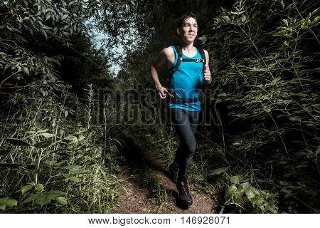 Trail running athlete moving through dark forest