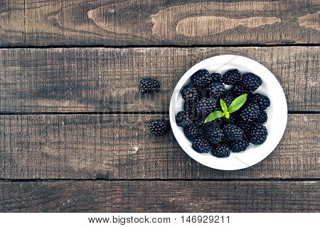 Close Up Of Ripe Blackberries In A White Ceramic Bowl Over Rustic Wooden Background. Top View.