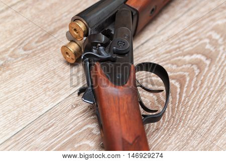 dubbelbarreled shotgun with bullets on wooden background
