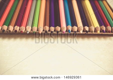 Colored pencils angle / Many different colored pencils on cement background