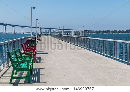 Park benches on pier at Cesar Chavez Park in San Diego, California, with Coronado Bridge in the background.