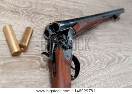 double-barreled hunting rifle closeup on wooden background