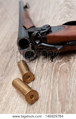 dubbelbarreled shotgun with two bullets on wooden background