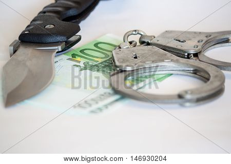 Handcuffs with knife on money background business security concept