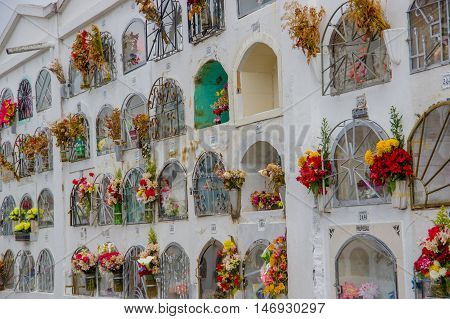 TULCAN, ECUADOR - JULY 3, 2016: vertical graves with some flowers at the side of each one.