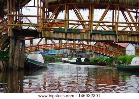 PASTO, COLOMBIA - JULY 3, 2016: some green boats parked under two bridges in a river close to la cocha lake.