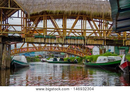 PASTO, COLOMBIA - JULY 3, 2016: some wood bridges standing over some boats on a river close to la cocha lake.