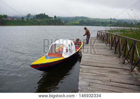 PASTO, COLOMBIA - JULY 3, 2016: unidentified man parking a nice small yellow boat next to the shore in la cocha lake.