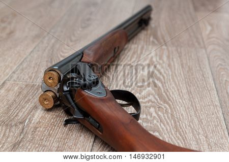 A wooden retro shotgun with shotgun shells on wooden background