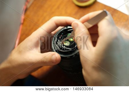 Engineer repairing camera lens in raw workplace