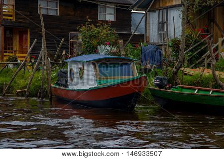 PASTO, COLOMBIA - JULY 3, 2016: colorfull boat parked next to a green canoe infront of some houses in la cocha lake.