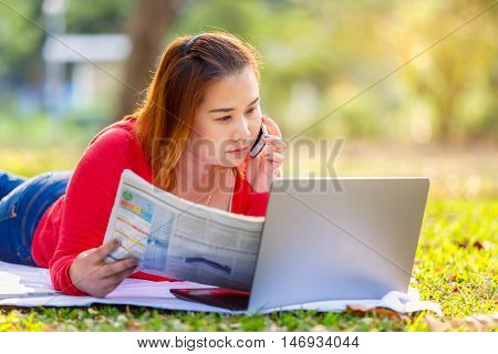 Business asian woman reading newspaper and working with laptop on the grass in park and talking on a phone