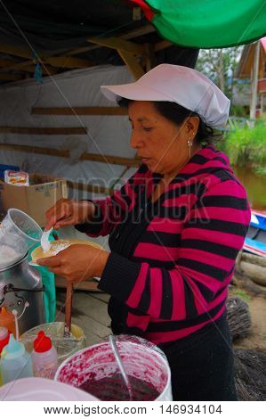 PASTO, COLOMBIA - JULY 3, 2016: unidentified woman adding some coconut to a dessert.