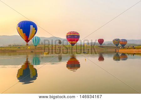 Hot air color balloon over lake with sunset time Chiang Rai Province Thailand