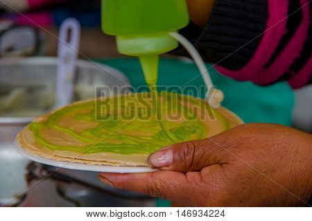 PASTO, COLOMBIA - JULY 3, 2016: woman adding some kiwi syrup to a wafer in a location close to la cocha lake.