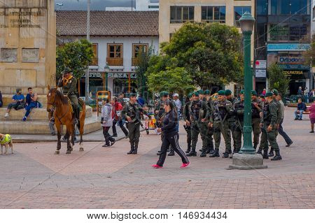 PASTO, COLOMBIA - JULY 3, 2016: unidentified pedestrians walking trough the center square, policemans holding guns.