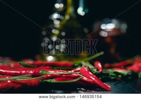 olive oil, baked tomatoes and chilli on black background