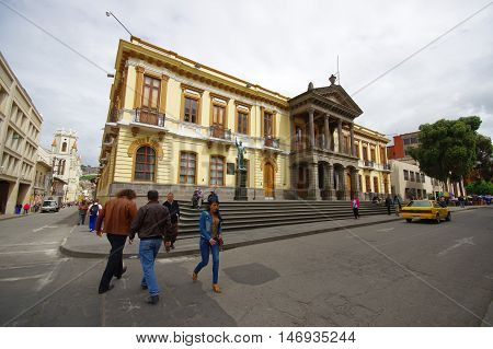 PASTO, COLOMBIA - JULY 3, 2016: some people crossing the street in front of the government building of the city.