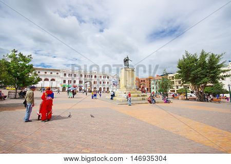 PASTO, COLOMBIA - JULY 3, 2016: pedestrians walkin on the central square where a statue of antonio narino is located.