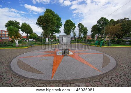 TULCAN, ECUADOR - JULY 3, 2016: sunclock located in the middle of a park with some trees as background.