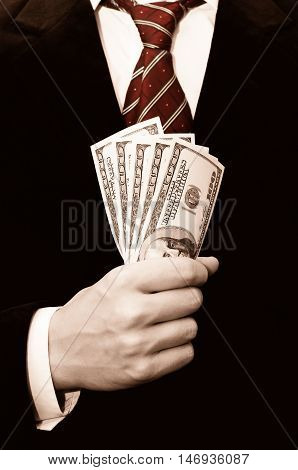 Businessman in black suit with dollars in his hand