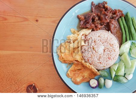 Rice mixed with Shrimp Paste in blue dish. Thai food on wooden background.