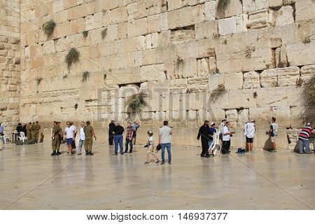 JERUSALEM, ISRAEL, OCTOBER 24, 2013, Jewish  soldiers, along with other worshipers praying at the mens side of the Western Wailing Wall which is also known as the Kotel, the most holy site for Jews in Jerusalem, Israel.
