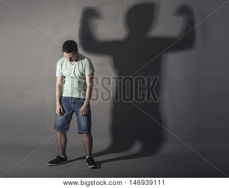 Image of a weak man standing depressed in front of a wall and his shadow shows streght