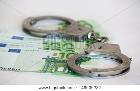 Silver handcuff and euro bank notes on white background