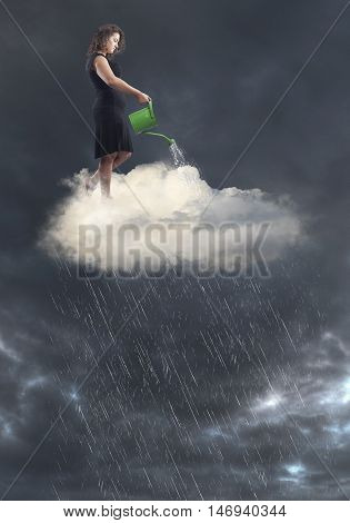 Woman in black dress standing over a cloud creating rain with watering can