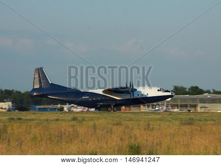 Kiev Region Ukraine - June 9 2011: Antonov An-12 cargo plane is taking off from the airport in the evening - side view