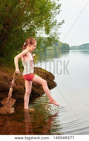 Little Girl With An Umbrella In Cloudy Day Near The Lake